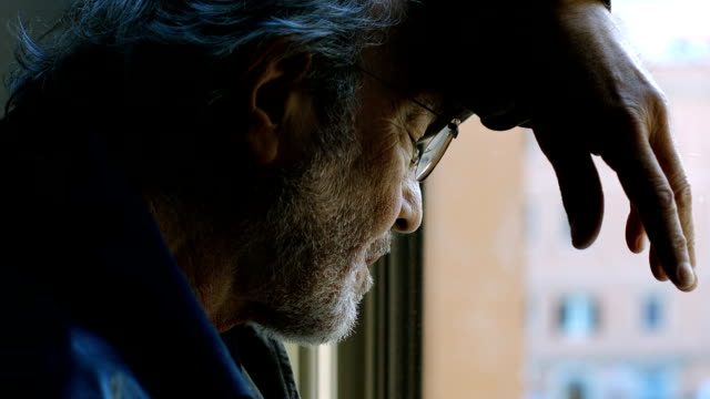 Elderly man looking out window with lonely expression video