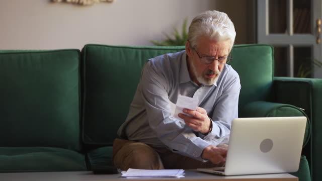 vídeos y material grabado en eventos de stock de el anciano maneja el presupuesto personal usando calculadora calcula gastos - planificación financiera