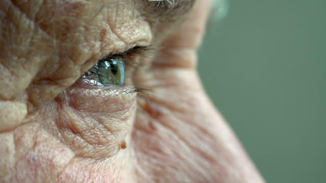 elderly man opens his eyes: old thoughtful man's eyes video
