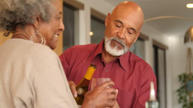 vídeos de stock, filmes e b-roll de homem idoso que derrama o vinho no vidro para a esposa em casa - vegetarian meal