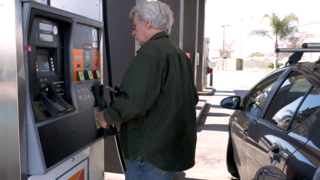 Elderly man pumping gas into his car from a self serve gas station Attractive elderly man pumping gas into his car from a self serve gas station during the day alternative fuel vehicle videos stock videos & royalty-free footage