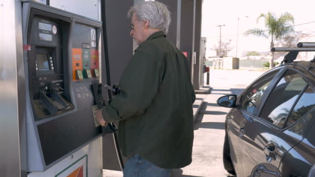 Elderly man pumping gas into his car from a self serve gas station
