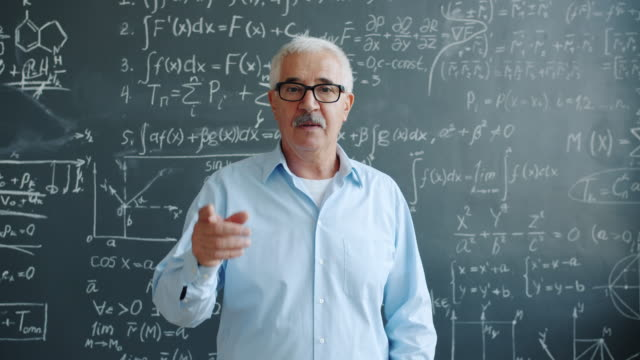 Elderly man raising finger and smiling having good idea in class with chalkboard video