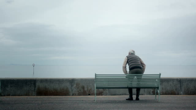 stockvideo's en b-roll-footage met elderly (senior) man sits by the seaside - eenzaamheid