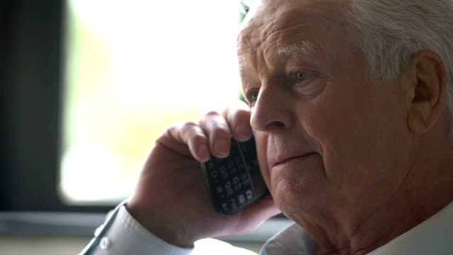 elderly man sits in a chair and speak at phone in a modern apartment video