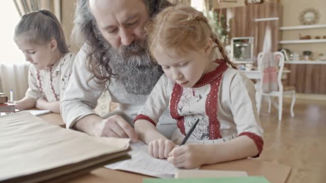 elderly man teaching kids in homeschool - славянская культура стоковые видео и кадры b-roll