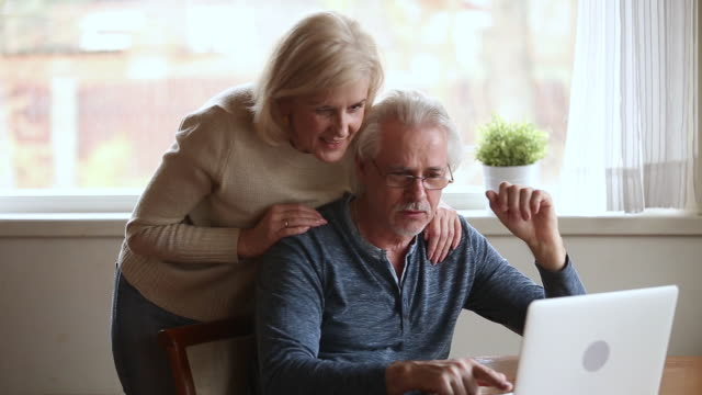 Elderly married couple internet users surfing web site at home