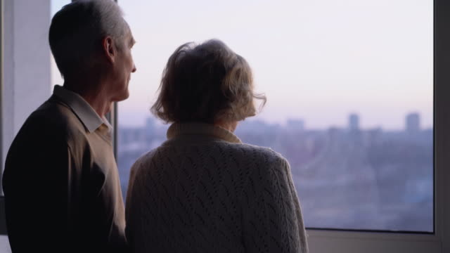 vídeos de stock e filmes b-roll de elderly married couple standing by window together, caring husband hugging wife - future hug