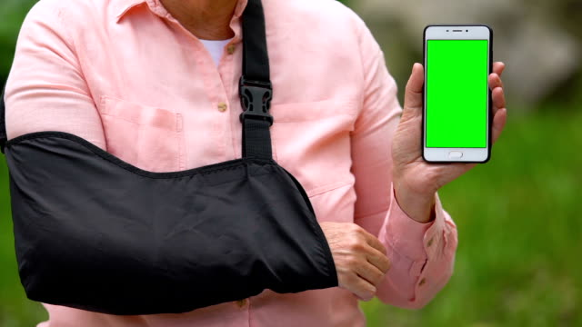Elderly patient in arm sling showing smartphone with green screen outdoors