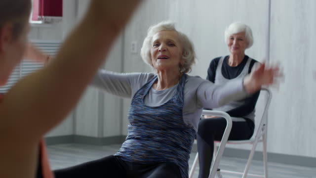 Elderly People Doing Chair Fitness Workout Medium shot of female fitness trainer and senior women in sportswear sitting on folding chairs and doing exercises: they are raising their arms and stomping feet chair stock videos & royalty-free footage