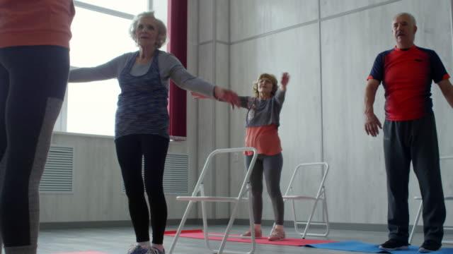 anziani che si allungano in classe fitness - dorso umano video stock e b–roll