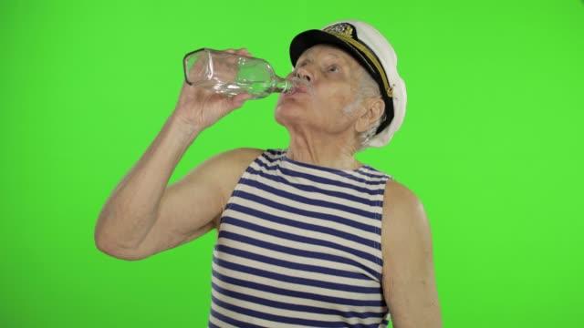 elderly sailor man with mustache drinks vodka. old sailorman on chroma key - vodka video stock e b–roll