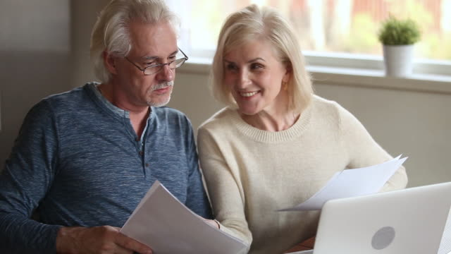 Elderly satisfied spouses holding bills makes easy online payments