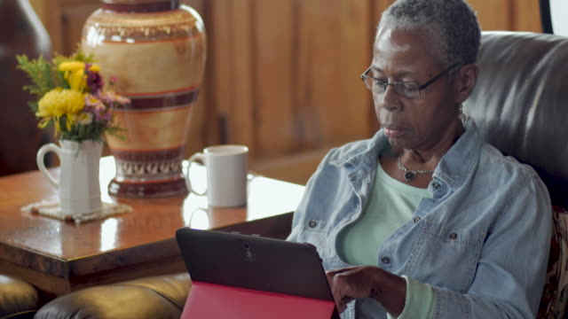 Elderly senior black woman using her digital tablet in her living room