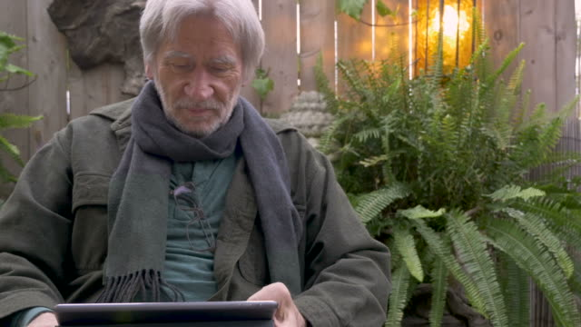 Elderly senior man reacting to his tablet shaking his head yes and no video