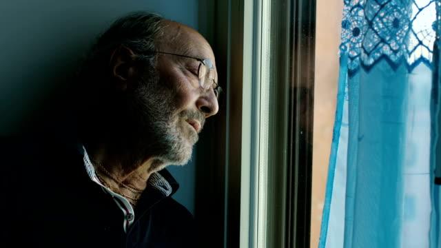 Elderly senior man standing next to window, alone video