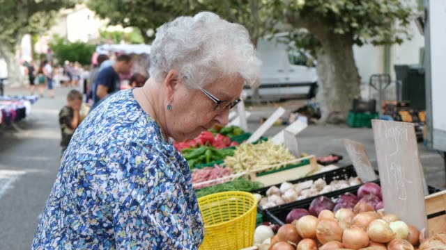 elderly senior woman buying fresh vegetables and fruits in farmer's market during summer day in provence france