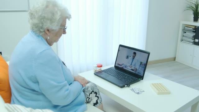 elderly senior woman, having remote medical consultation with her doctor over internet computer telemedecine diagnostic 4k 50fps footage - telemedicine stock videos & royalty-free footage