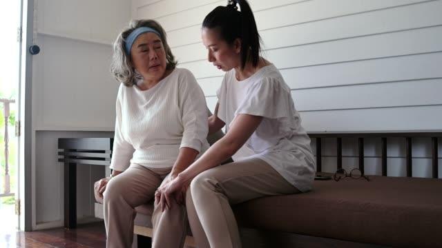 yaşlı yaşlı kadın kanepede otururken dizlerini acıyor - orta yetişkin stok videoları ve detay görüntü çekimi