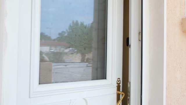 äldre senior kvinna öppnar dörren till sitt hus och välkomnande människor hemma - ytterdörr bildbanksvideor och videomaterial från bakom kulisserna