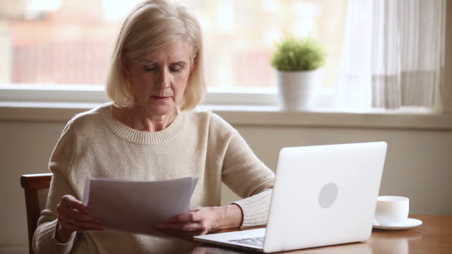 Elderly stressed woman holding bills use laptop check online payments