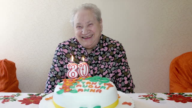 elderly woman and one blows out the candles on her birthday: loneliness, aging, video