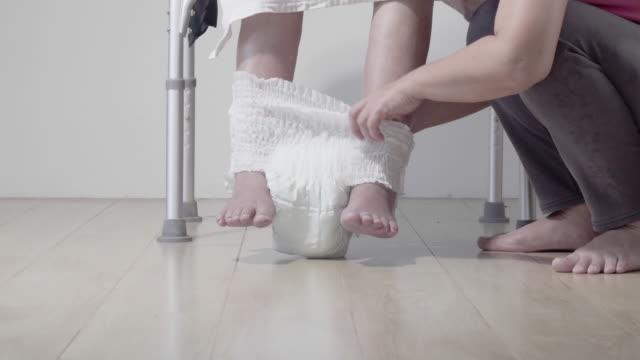 vídeos de stock, filmes e b-roll de fralda em mudança da mulher idosa com cuidador - geriatria