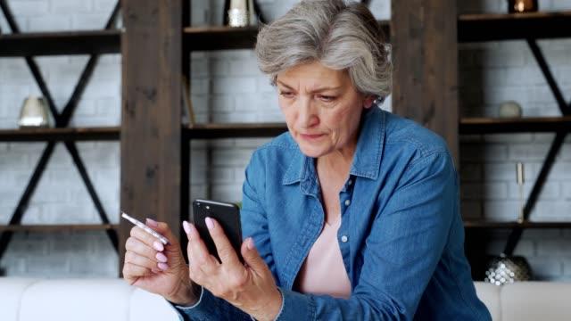 vídeos y material grabado en eventos de stock de una anciana revisa la receta usando su teléfono inteligente. sostiene un teléfono inteligente en una mano y píldora en la otra - recipiente para las píldoras
