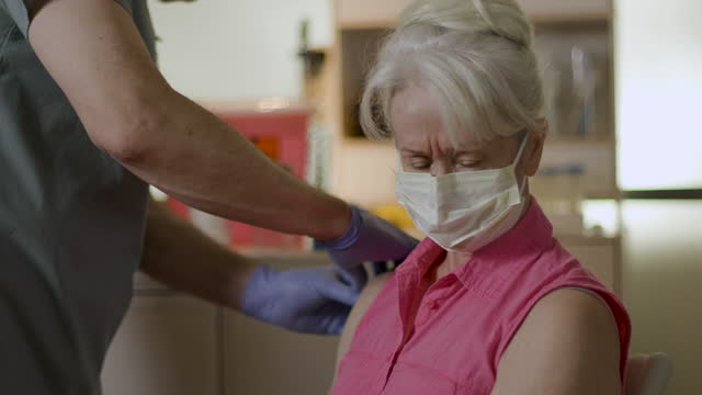Elderly woman getting covid vaccine shot.mov A senior Caucasian woman sitting in a clinic wearing a mask is injected with a vaccine to prevent SARS-CoV-2 better known as COVID 19. covid vaccine stock videos & royalty-free footage