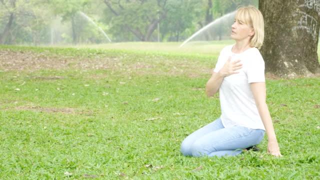vídeos de stock e filmes b-roll de elderly woman having heart attack suddenly in the park. - coração fraco