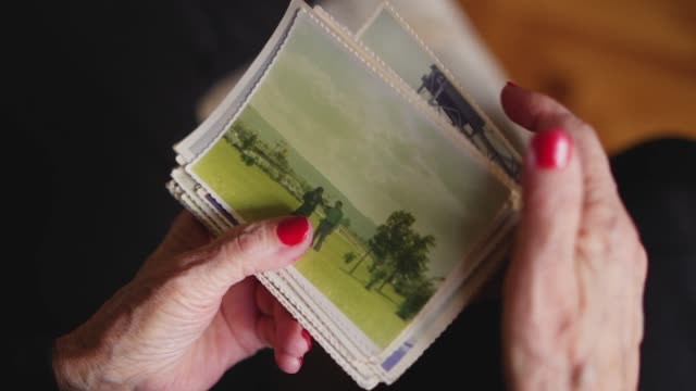 elderly woman holding old photo of her husband - rispetto video stock e b–roll