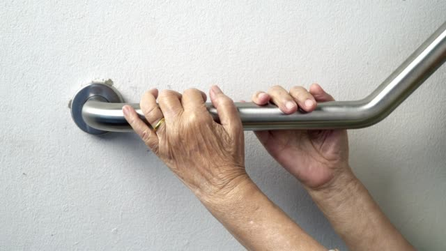 Elderly woman holding on handrail for safety walk steps video