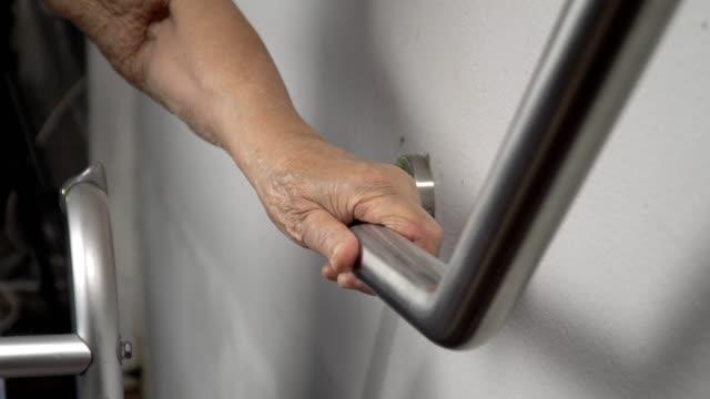 vídeos y material grabado en eventos de stock de anciana, aferrándose a la barandilla de seguridad dar pasos - geriatría