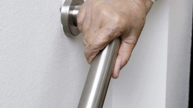 elderly woman holding on handrail for safety walk steps - parapetto barriera video stock e b–roll