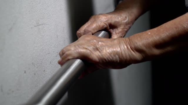 Elderly woman holding on handrail for support walking video