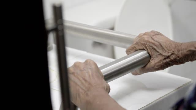 elderly woman holding on handrail in bathroom - parapetto barriera video stock e b–roll