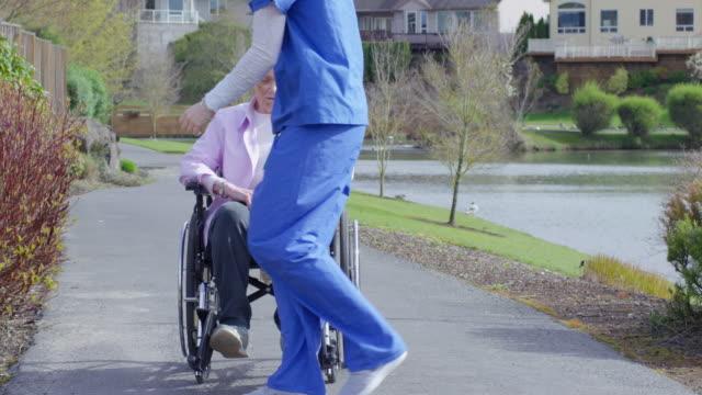 vídeos y material grabado en eventos de stock de ancianos disfrutando de la mujer en silla de ruedas al aire libre con su cuidador - deportes en silla de ruedas