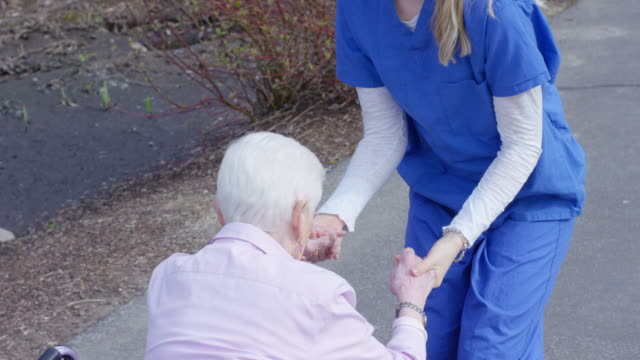 Elderly woman in wheelchair enjoying the outdoors with her caregiver video
