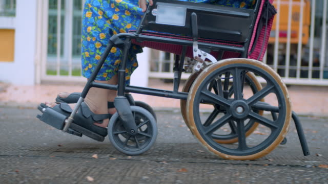 Elderly woman in wheelchair enjoying the outdoors with her caregiver,Slow motion Elderly woman in wheelchair enjoying the outdoors with her caregiver,Slow motion pushing wheelchair stock videos & royalty-free footage