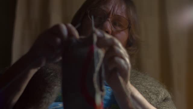 Elderly woman knitting a sock from wool yarn