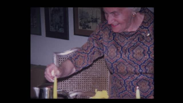 vídeos y material grabado en eventos de stock de 1971 anciana enciende velas para iniciar la seder de la pascua - pascua judía