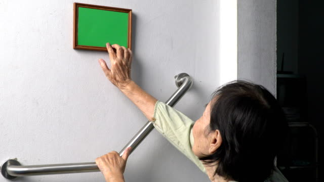 Elderly woman looking at a memories photo on wall , (green screen) video