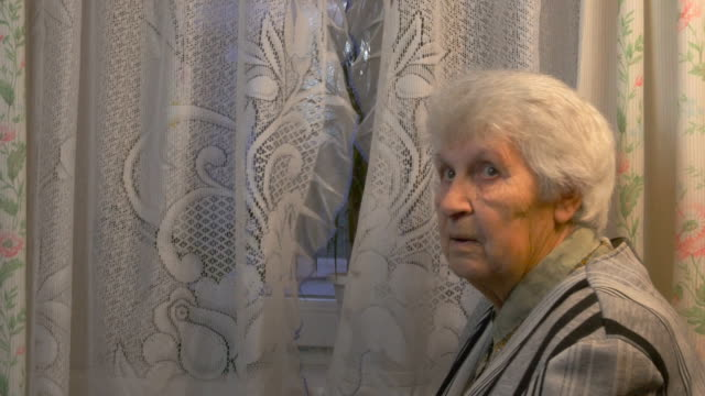 Elderly woman looking to window video
