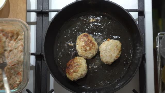 주철 프라이팬에 팬 튀김 치킨 커틀릿을 만드는 노인 여성 - burger and chicken 스톡 비디오 및 b-롤 화면