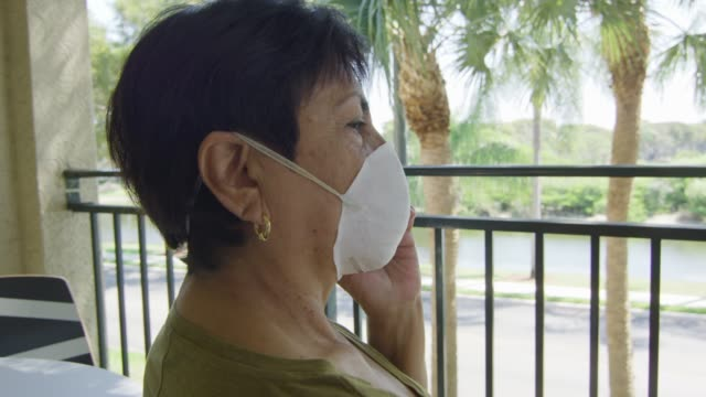 Elderly woman on balcony talking on the phone while wearing face mask video