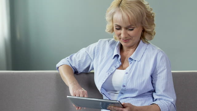 Elderly woman on sofa scrolling tablet screen and smiling, looking at pictures video