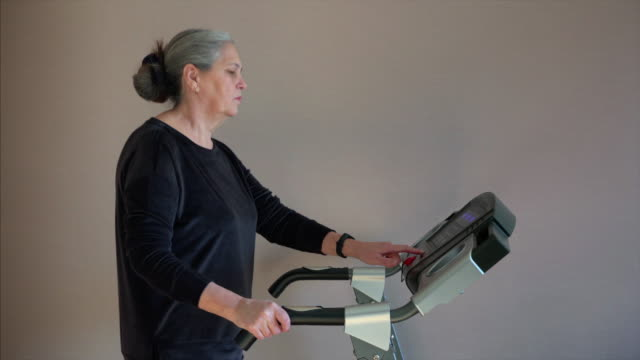 elderly woman pressed button to change training walking mode. - runner rehab gym video stock e b–roll