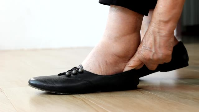 Elderly woman putting on shoes. Elderly woman putting on shoes. ankle stock videos & royalty-free footage