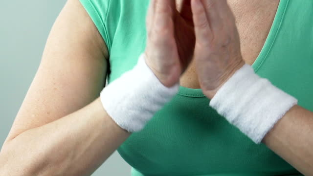 Elderly woman putting palms together at her chest, practicing yoga, close-up video