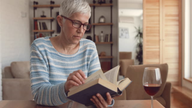 Elderly woman reading a book and enjoying in relaxing day at home. video